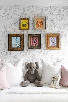 Wallpapered kids room with rabbit paintings and stuffed elephant.