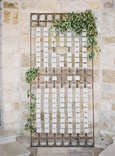 escort cards elegantly displayed on an iron gate with greenery