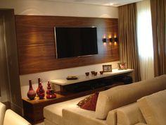 Painel da TV com arandelas é o destaque desta sala com 3 ambientes
