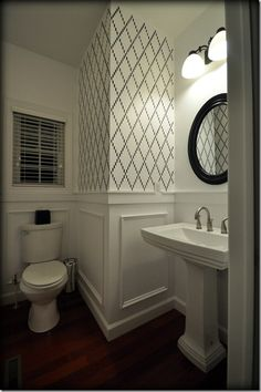 Black & white bathroom makeover features Nova Trellis Stencil by Royal Design Studio.  Note: the stencil was not used on the wall behind the stool and the sink, which prevents the design from being too overwhelming.