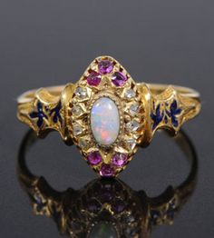 Victorian gold (18ct) opal, diamond, ruby and enamel dress ring, the marquise-shaped cluster with a central oval opal surrounded by ten rose cut diamond chips to the sides and six small rubies to the top and bottom of the bezel, with engraved gold shoulders with blue enamel leaves on gold shank (Birmingham 1870).