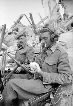 New Zealand soldiers admire a puppy that was found in the ruins of a house captured by the New Zealand Infantry during the Italian Campaign. Sesto Imolese, Emilia-Romagna, Bologna, Italy. 16 April 1945. Image taken by George Kaye. Pin by Paolo Marzioli