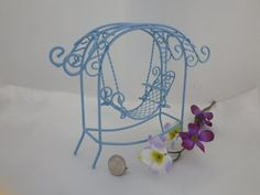 This light blue swing will be relaxing to any miniature guests in the fairy garden or doll house flower garden.  This swing measures 5 inches tall and 6 inches wide at the top and is metal.  Request any custom color.
