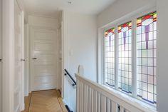 Jaren30woningen.nl | Stijlvolle overloop met grote glas in lood ramen en vijfvlaks paneeldeuren
