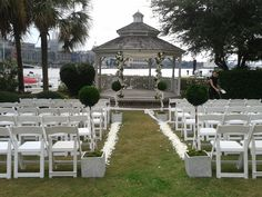 Preserved boxwood topiaries line the aisle for a modern garden ceremony.  Floral design by http://www.harveydesigns.com