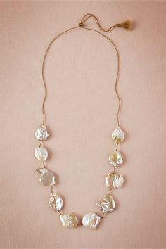 """Estuary Necklace from BHLDN ten baroque pearls, golden-blush in color and subtly iridescent, are hand-knotted for a simple yet striking necklace. Limited Edition. Due to subtle variations in the pearls, no two necklaces are alike. 35""""L, 1""""W. Slide knot closure. Freshwater pearl, nylon. Handmade. Imported. Layers nicely with the Asterism Necklace."""