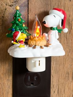 Peanuts Christmas Campfire Night Light: Huddled by the light of a flickering campfire, Snoopy and Woodstock wait patiently for Santa's arrival. With a plug that swivels 360° to fit any outlet and a convenient on/off switch, this fun Christmas night light subdues the darkness as only the Peanuts can, with good cheer and a warm glow.