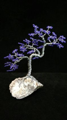 This is the Upflo tree made in stainless steel wire. The leaves of this tree are made by looping purple seed beads on the wire that is twisted to create the shape of the branches. The trunk cascades upwards with branches at random intervals. The leaves give a dazzling display when showed under a light. The tree is securely mounted to a natural stone found along the banks of the Mekong River in Thailand. Furniture pads are adhered to the bottom of the stone to protect any surface that you…