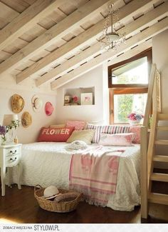 bed in corner, pillows along wall