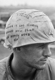 "At the forward Marine artillery base in Con Thien, South Vietnam, which had been mercilessly pounded by North Vietnamese big guns, Cpl. Billy Winn of Cabot, Arkansas, added a touch of sardonic humor to the situation with a message penned on his helmet cover. The inscription ""Where is Lee Harvey Oswald now that we really need him,"" refers to the ex-Marine who assassinated President Kennedy. October 13, 1967."
