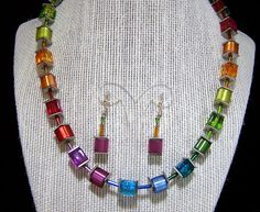 Vintage USA artist made square lucite bead jewelry set Rainbow hued beads alternate transparent and frosted square lucite beads, with flat silver tone squares and glass bugle beads Full range of colors purple, red, orange, olive green, teal, and blue Sterling silver lever back earrings have a frosted purple bead, signed and tested 925 Silver plated lobster claw clasp 16-18 inches long necklace, each square is 3/8 inches square Unsigned Very good vintage condition, shows no wear I special...