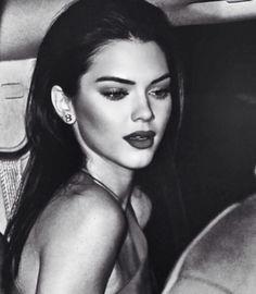 Slicked back hair, red lip, smokey eyes.