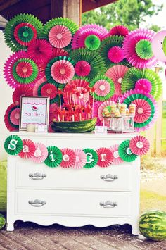 Watermelon party: backdrop is store-bought tissue paper fans in different sizes, layered with DIY paper medallions