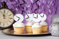 "Use cardstock, glitter, scissors, and other craft items to create simple ""clock cupcake toppers""! You can stick these down in everything from appetizers to desserts (think beyond the cupcake!)."