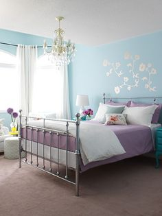 not these flowers because they are way too girly for M but it would be pretty easy to find a cool stencil design and paint a white design on the blue wall over her bed.