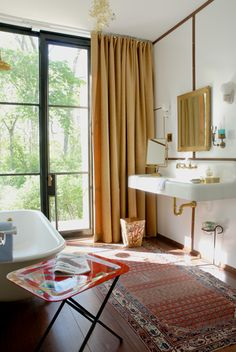Glass House, East Hampton  Photo: Barbel Miebach Sign of the Crab faucet, vintage farmhouse porcelain sink, vintage clawfoot tub, sconces from Olde Good Things, Tord Boontje Garland brass pendant light, painted Masonite boards with mahogany details, Piero Fornasetti tray table.
