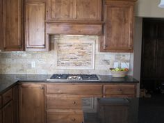 Kitchen back splash with decorative piece over cooktop.  Subway tile in varying colors.  framed decorative piece.  knotty alder cabinets with medium stain, classic and never outdated.