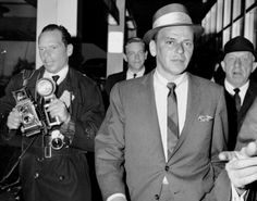 Looking smart in a two-piece suit, Frank Sinatra gets hounded by photographers at JFK Airport as he returns from Europe in 1964.