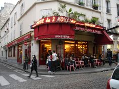 """The Café des 2 Moulins (French for """"Two Windmills"""") is a café in the Montmartre area of Paris.a comfy neighbourhood café – minus the tobacco counter, which has been nixed in favour of more sitting room. The scatter of tables and bright red chairs on the sloping pavement is the perfect vantage point from which to observe the lively street market. It was featured in the film 'Amélie'."""