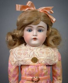 """With what poets might call an """"alabaster brow"""" this Kestner girl is a real princess. Her blue eyes and golden synthetic curls stand out against her pale bisque and her pink-and-yellow cotton dress with lace trim matches the pink silk bow in her hair. Will you be the one to give this poetic beauty a home? Find her on our Ruby Lane page priced at $600. #antiquedoll #antiquedolls #antiquedollshop #dolls # #victorian #steampunk #antique #antiques #antiqueclothing #antiquetextiles #красиваякукла…"""