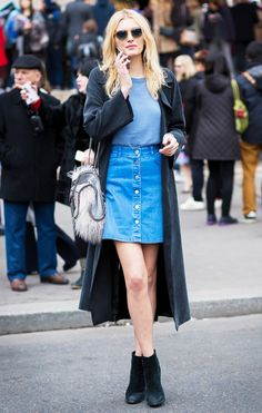 Lily Donaldson in a button up denim skirt, cape, and black booties