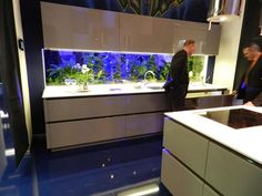 """New Crazy Cool Idea from Bauformat: Fish tank as a backsplash for your kitchen. Simple high-gloss white kitchen cabinets.Handles kitchen cabinets with """"touch to open"""" mechanisms. Huge drawers with pull-out units. Fish tank will make Your kitchen a ce"""