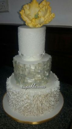 The classy n elegant wedding cake incorporating many elements like edible lace, wafer paper, ruffles and a sugar flower !!