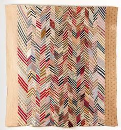 Chevron Strippy   1880 - 1900  A colourful cotton and wool strippy Chevron quilt, hand quilted and hand and machine sewn. Strips of fabric pieced in 'V's in log cabin style to make long lengths. The lengths were then joined together to create a zig-zag effect across the quilt. Quilted in straight zig-zag and diagonal lines.