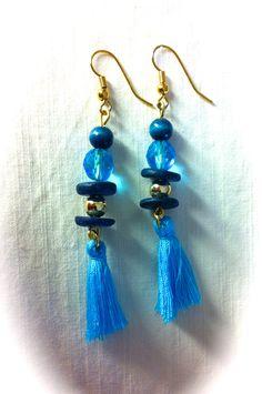 Pendientes con cristales facetados, piezas de madera bolita metálica y pompones de algodón azul: 6€