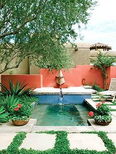 a garden with a red wall and a small pool
