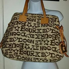 Dooney & Bourke Large Brown Logo Handbag. *FLASH SALE UNTIL*Price will go back to  $75 shortly *I'm not accepting offers for this. Priced to sell. Dooney & Bourke Large Brown Logo Handbag.  Authentic. Has hot pink Dooney & Bourke liner. Some discoloration from use. Not very noticeable because of the brown colors. You are purchasing this bag as is. This is not an outlet bag.  No trades Dooney & Bourke Bags Shoulder Bags