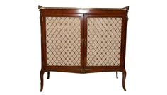A Victorian mahogany chiffonier, the top with pierced brass three-quarter gallery above a cockbeaded pair of pleated mesh silk-lined brass trellis doors, on sabre feet with brass decor.                                                                                                                         C.1900