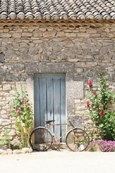 Southern France - rustic stone wall with flowers in front.