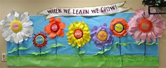 Checkout this great post on Bulletin Board Ideas!  The 3d flowers are made by cutting out petals and taping floral wire to the back of each one to allow them to shaped.  The middle is made from felt covered paper plates stuffed with batting.  The stems are sticks.  Pretty simple!