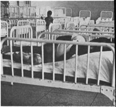 Christmas In Purgatory: A Photographic Essay On Mental Retardation . 1972, Blatt & Kaplan  A child lying in bed with side rails in a room filled with identical beds.