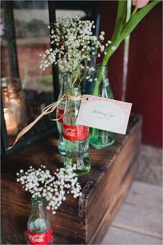 Baby's breath in coke bottles -- very cute. Reminds me of my dad bringing in roses from the backyard and putting them in whatever random bottles we had in the house. Photo by Kristyn Hogan #cedarwoodweddings