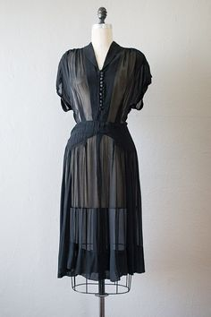 1940s black sheer silk chiffon dress. Vintage 40s dress features extended sleeves with shirring on the shoulders, buttons all along the bodice and multiple darts, and flared skirt with ruche details on the hips. Sheer.