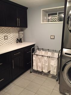 This is my new laundry room. Didn't get to use the wood looking tiles. I guess your floor has to be perfectly flat and even, or with a tile that is long and skinny they would crack when putting weight on them. Paint color is krypton from Sherwin Williams. We used white marble countertop. Black cabinets from cabinets to go.