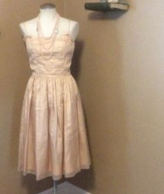 Adorable authentic vintage madmen style vintage dress. No tags Indicating size or material, so check measurements for the best fit. Peachy Tan in color,  appears to be made of Taffeta with a mesh overlay. Spaghetti straps with zipper in the back.  Waist measures 26 inches bust measures 34 inches 43 inches in length. Dress is an amazing vintage condition. $50 shipped