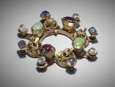 Annular brooch; gold, emeralds, pink and blue sapphires, pearls; of circular form with eight bosses; the bosses alternately openwork set with a winged beast, emerald, pink sapphire; from each boss a projection set alternately with pearls and sapphires; Culture/periodLate Medieval term details Date14thC
