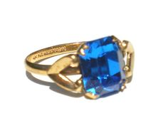 Gorgeous Art Deco style ring with a dark blue glass stone set on a gold tone band, signed by Uncas. Size 5.5 Check out Ribbons Edge for more great pieces of vintage and antique jewelry
