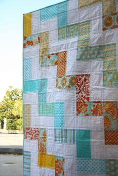 You could probably do this with a jelly roll (in color and in white) - sew two long strips together, cut them to make square blocks, and piece the square blocks together alternating horizontal and vertical orientations to get the zigzag effect.