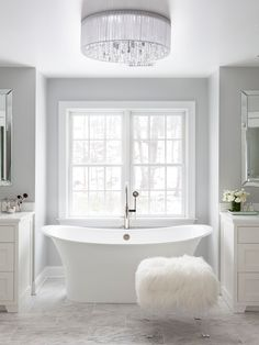 Susan Glick Interiors - bathrooms - his and her vanities, his and her washstands, his and her bathroom vanities, white vanity, white quartz countertop, bathtub nook, crystal flushmount chandelier, beveled mirrors, gray walls, gray bathroom walls, white and gray bathroom, white and gray master bathroom, marble tiled floor, lucite ottoman, shag ottoman,