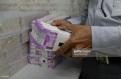 An Indian bank employee checks stacks of new 2000 rupee notes in Ahmedabad on November 11, 2016. Long queues formed outside banks in India as people crowded in to deposit old currency and withdraw new notes after the two largest denomination rupee notes were taken out of circulation. / AFP / SAM