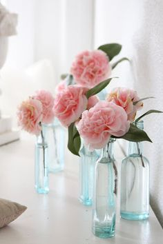 Pretty pink roses in light blue vases go beautifully together.