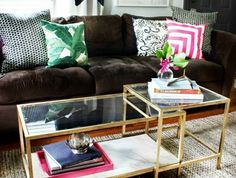 2-table-de-salon-en-verre-et-fer-or-fleurs-sur-la-table-canape-marron-coussins-decoration