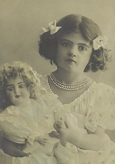 Antique photo of girl with doll circa 1900 - 1910.