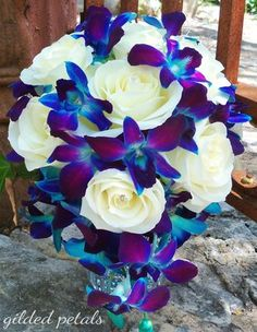 Pretty bridal bouquet with white roses and blue and purple orchids.