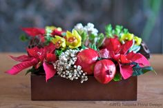 Winter box of pomegranate, poinsettias, and orchids from Tulipina Floral Design in Burlingame, CA. $150.00