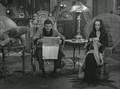 "Gomez and Morticia chat in his and hers chairs beside the two-headed turtle. Those wicker chairs with the wide, rounded backs, became popular for awhile and were often referred to as ""The Morticia Chair."""
